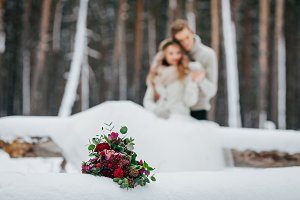 Bride and groom are sitting on the log in the winter forest. Close-up. Winter wedding. Soft focus on the bouquet