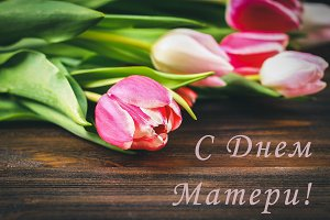 Pink tulips on wooden table with an inscription in Russian - Happy Mother's Day