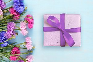 Cornflowers and gift box on blue