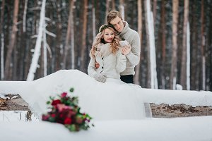 Bride and groom are sitting on the log in the winter forest. Close-up. Winter wedding. Soft focus on the couple