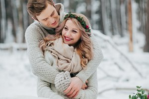Happy newlyweds are hugging in the winter forest. Couple in love. Winter wedding ceremony.