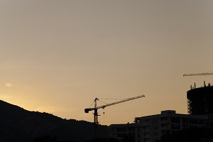construction cranes at sunset