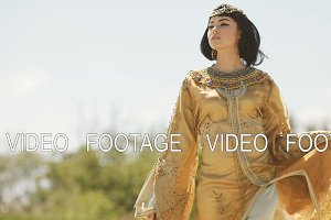 Beautiful woman like Egyptian Queen Cleopatra on in desert outdoor.
