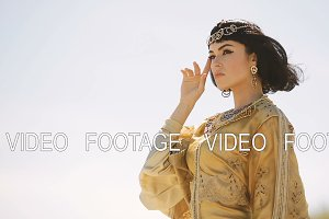 Beautiful woman with fashion make-up and hairstyle like Egyptian queen Cleopatra outdoors against desert windy weather
