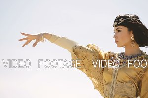 Beautiful woman with fashion make-up and hairstyle like Egyptian queen Cleopatra outdoors against sky