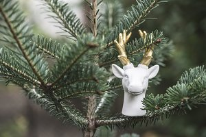 Statue of white deer on fir branch