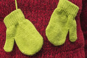 Winter green gloves on red sweater
