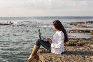 Freelance female with black laptop at the beach