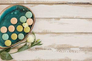Turquoise plate with pink and green macaroons over white rustic