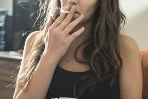 Girl smokes and holds ashtray