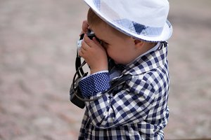 little boy holding retro camera