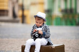 little boy holding a retro camera