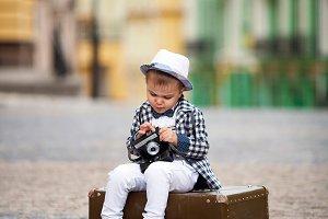 little boy holding a retro camera