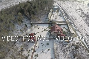 Winter countryside scene with houses, forest and snowy fields. Aerial view