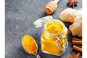 turmeric powder in glass jar and spoon