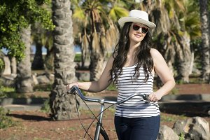 Young joyful woman with bike on vacation