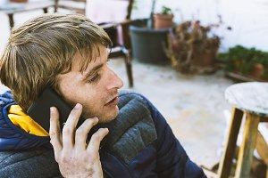 Handsome blond man, talking on mobile phone, sitting outside