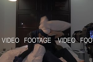 Making a footage of dad and son fight on bed