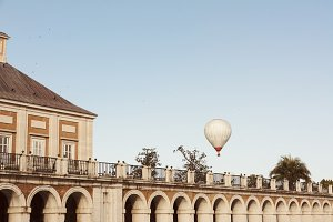 White hot air balloons flying in the sky, next to the Palace of Aranjuez, Spain
