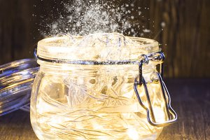 Magic Christmas garland with bright lights inside a glass jar