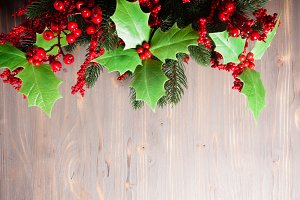 Holly and fir twigs on wood wall