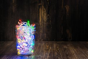 Christmas fairy lights in a glass jar. Home x-mas decor concept
