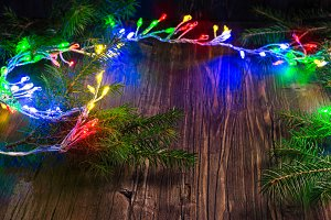 Magic Christmas garland with bright lights and fir tree branches on wooden background
