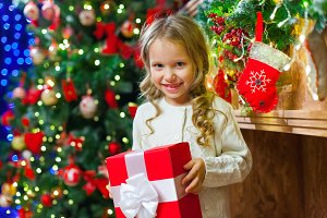 Little girl sitting by the tree holding a Christmas gift a lot o