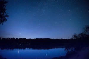night sky with many stars on a lake