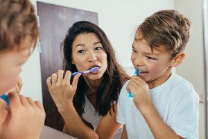 Mother and son brushing teeth