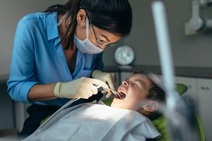 Pediatric dentist inspecting teeth