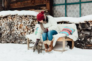 Woman stroking a cat in the snow