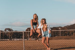Two female models posing by a fence