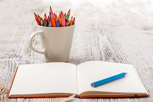 White cup with colorful pencils