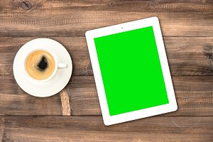 Tablet pc and coffee on wooden desk