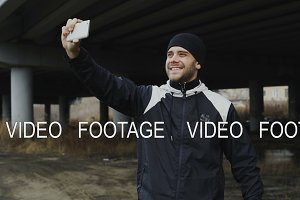 Happy sportive man taking selfie portrait with smartphone after training in urban outdoors location in winter