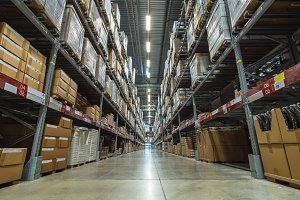 Large warehouse logistic or distribution center. Interior of warehouse with rows of shelves with big boxes
