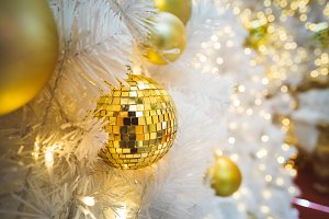 Golden bubble and many lights hanging as Christmas tree decoration. New year fir tree branch photography. Close Up decorated white Christmas tree for celebration with defocused lights background