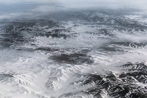 Aerial view above the Himalayas with city at center