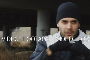 Slowmotion of concentrated man boxer doing boxing exercise in urban location outdoors in winter