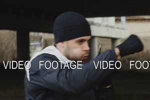 Slowmotion of sportive man boxer doing boxing exercise in urban location outdoors in winter