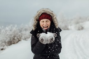 Blowing off snow from her hands