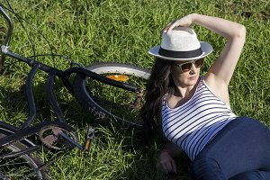 Female tourist with bike lying on gr