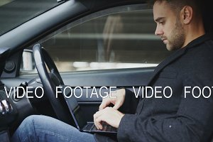 Attractive young man using tablet laptop computer while sitting inside his car outdoors