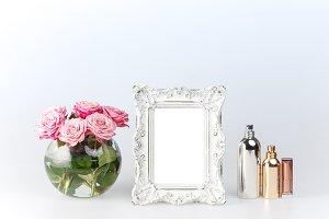 Flowers vase and vintage frame on white
