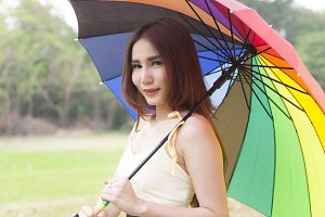Woman holding multicolored umbrella