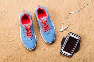 Sports shoes, earphones, smartphone against sand, studio shot.