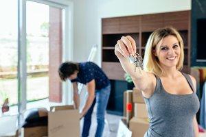 Woman showing keys while her husband unpacks
