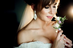 Gorgeous bride holds rose boutonnier