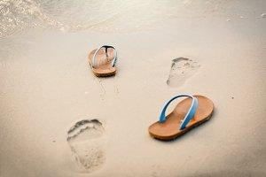 Blue sandal with footprint on beach